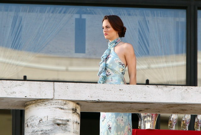 Leighton Meester in a light blue floral dress and chignon on a balcony