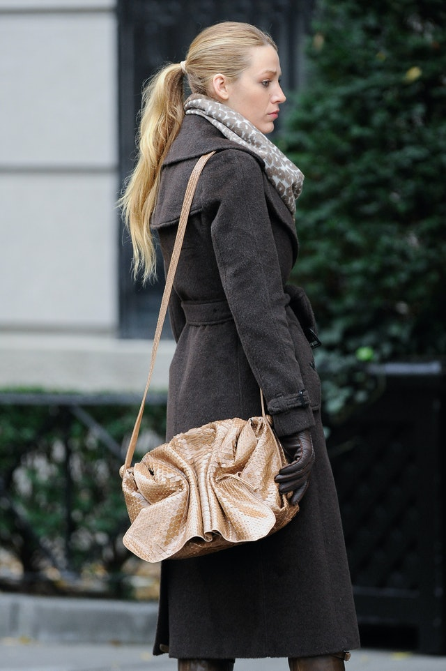 Blake Lively in a ponytail wearing a black wool trench coat