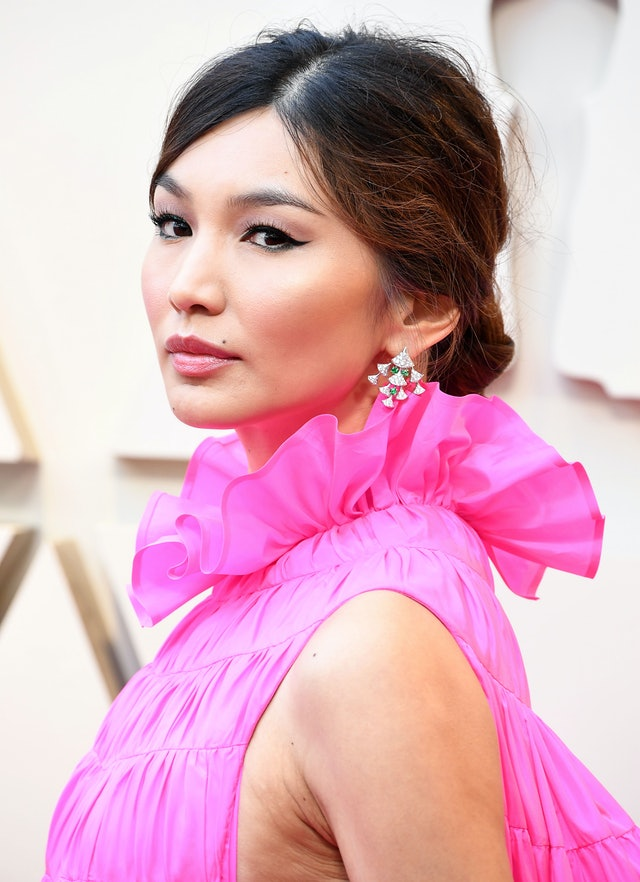 Gemma Chan's low bun was complemented by her bright pink dress and sparkling earrings