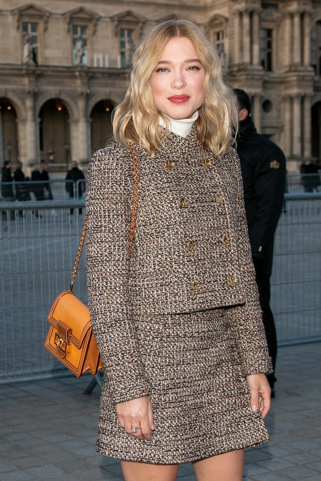 Lea Seydoux wears a rosy pink lipstick and tweed skirt and blazer outside of the Louis Vuitton show at Paris Fashion Week.