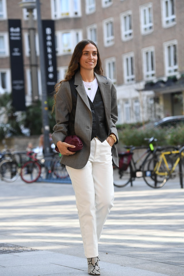 Street style photo of influencer Erika Boldrin wearing a tailored blazer over a leather vest with white jeans and snakeskin boots at Fashion Week.