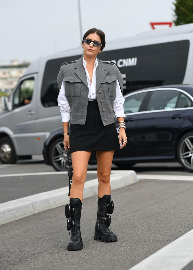 Street style photo of a woman wearing a boxy utility vest over a white button-down shirt and mini skirt with Prada combat boots at Fashion Week.