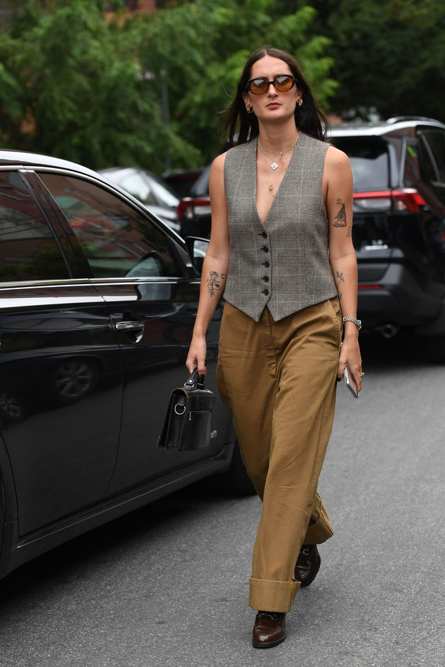 Street style photo of a woman wearing a tailored menswear vest at Fashion Week.