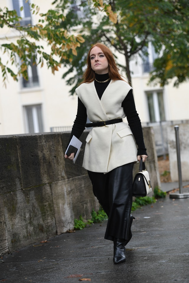 Street style photo of a woman wearing a belted white vest with a black turtleneck and leather skirt at Fashion Week.