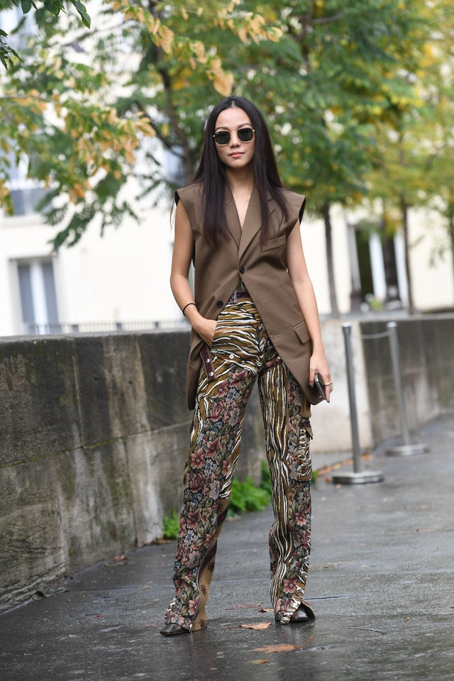 Street style photo of influencer Yoyo Cao wearing a long vest over statement print pants at Fashion Week.