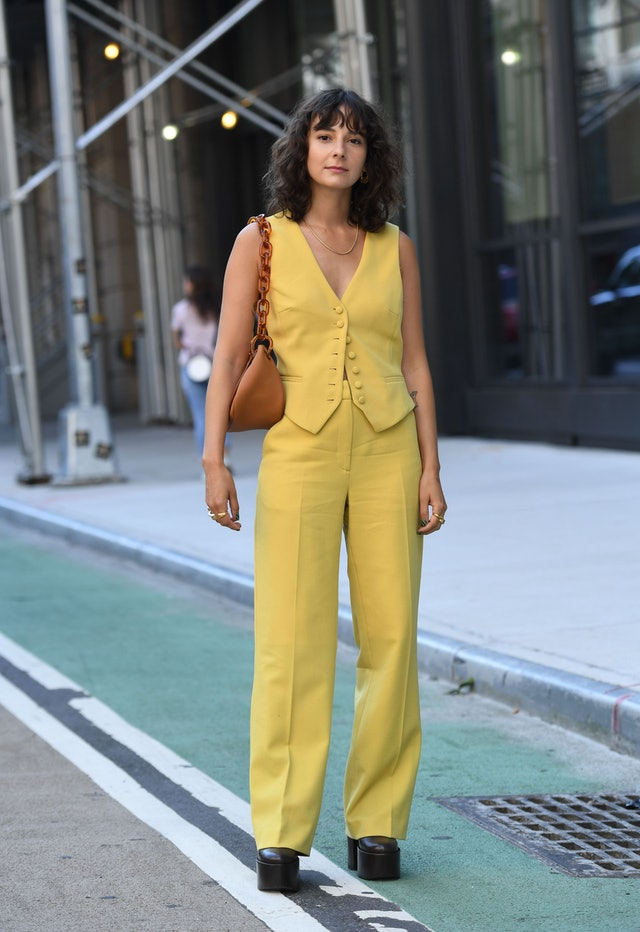 Street style photo of influencer Alyssa Coscarelli wearing a yellow vest and matching trousers with platform shoes at Fashion Week.