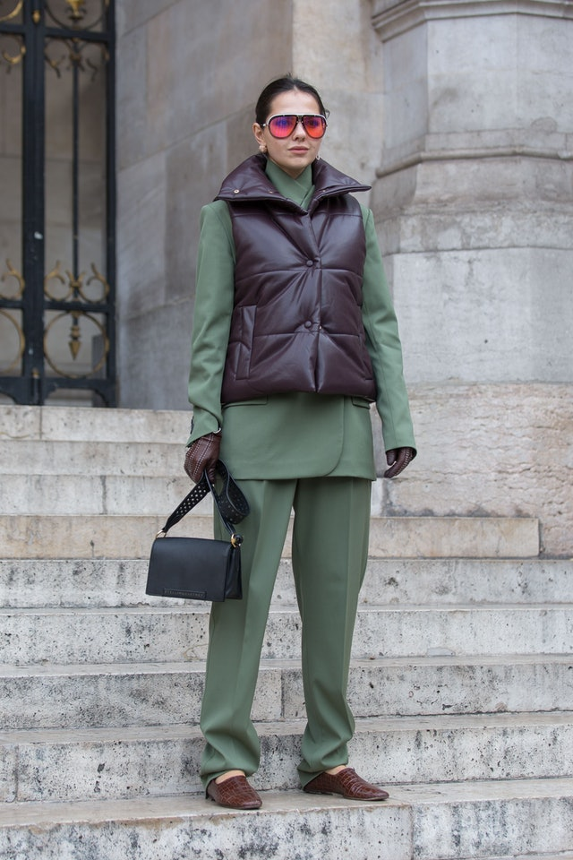 Street style photo of a woman wearing a puffer vest over a sleek green suit at Fashion Week.