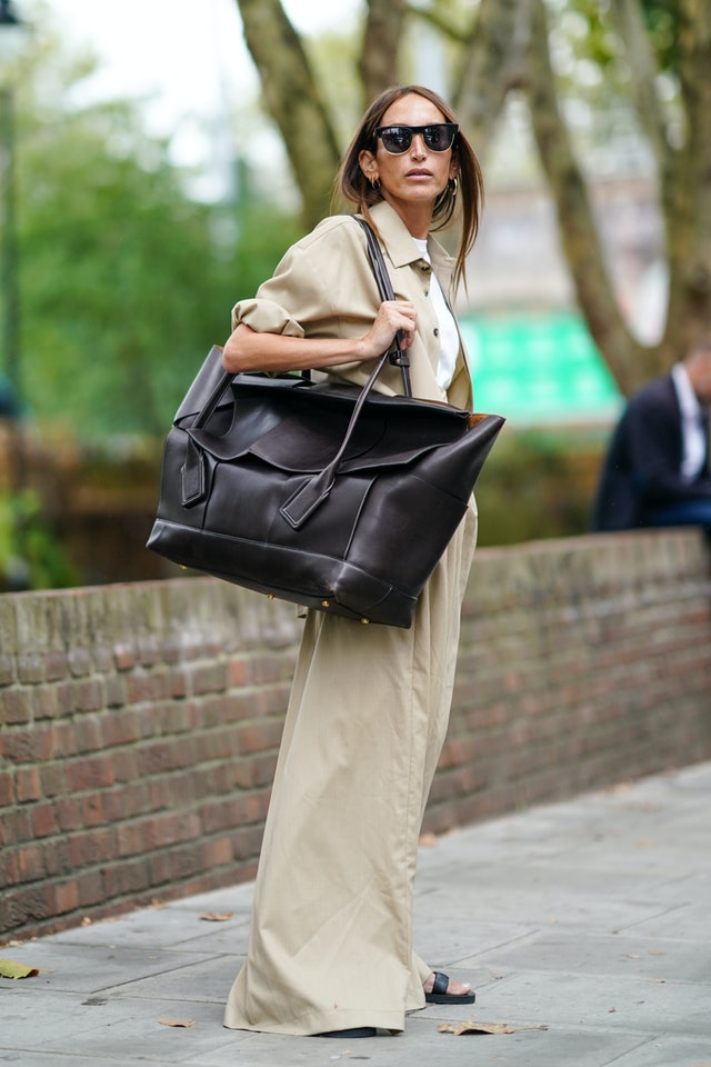 Street style photo of influencer Chloé Harrouche carrying an oversized Bottega Veneta bag at London Fashion Week Spring 2020.