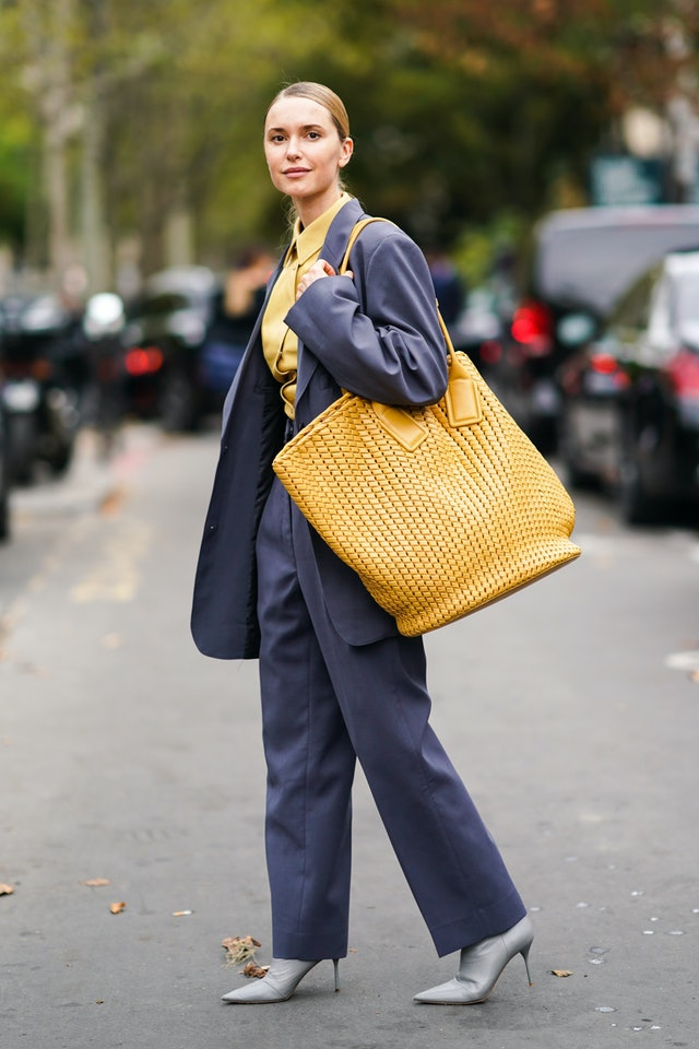 Street style photo of influencer Pernille Teisbaek carrying an oversized Bottega Veneta bag at Paris Fashion Week Spring 2020.