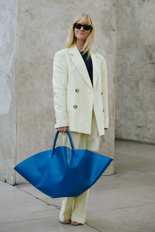 Street style photo of Jeanette Madsen carrying an oversized blue Jil Sander bag at Paris Fashion Week Spring 2020.