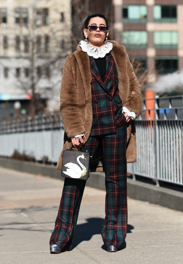 Street style photo of Cici Celia wearing a plaid suit over a ruffle-neck top with a brown fur coat at New York Fashion Week Fall 2019.