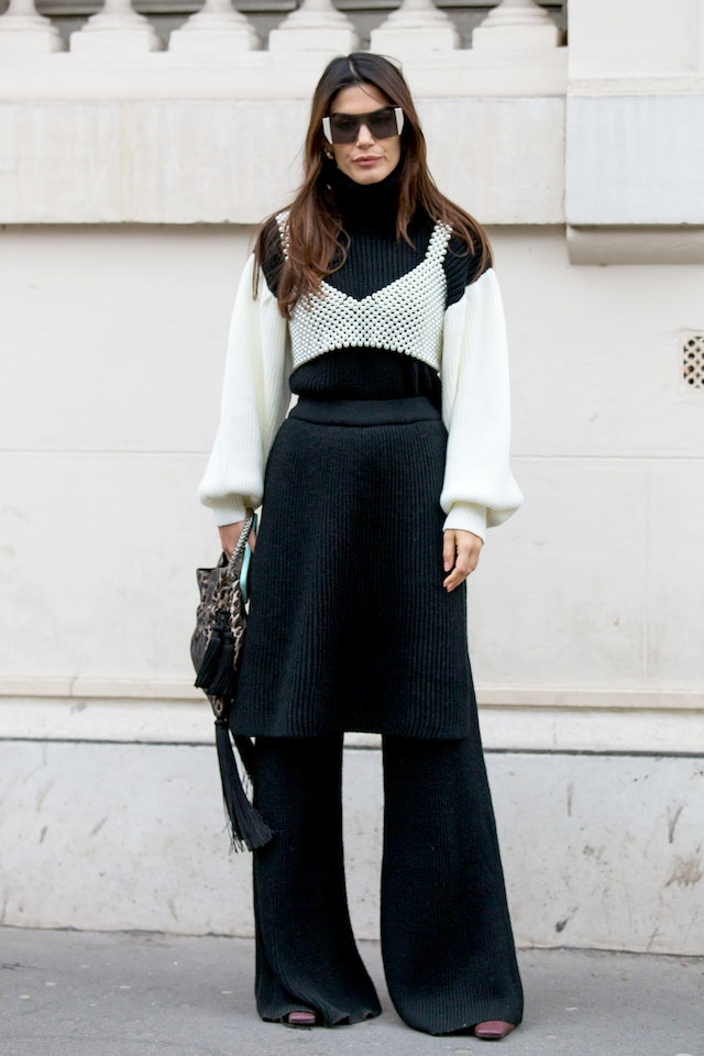 Street style photo of a woman wearing a black and white sweater layered under a pearl tank top with a black skirt and wide-leg trousers at Paris Fashion Week Fall 2019.