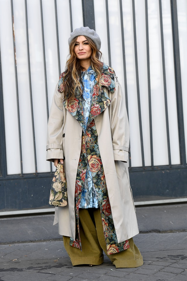 Street style photo of a woman wearing a floral shirtdress layered with a floral coat, trench coat, and wide leg pants at Paris Fashion Week Fall 2019.