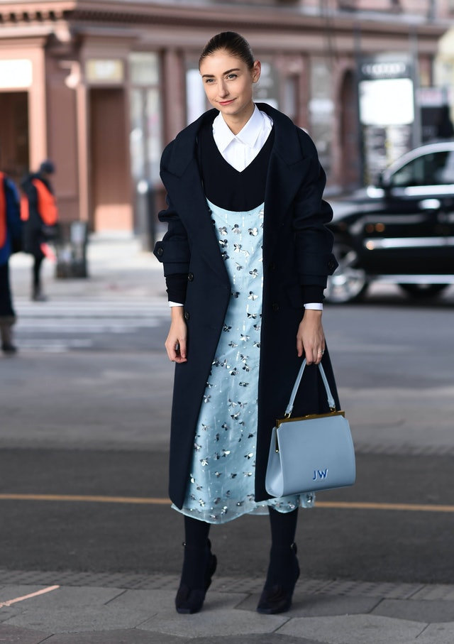 Street style photo of Jenny Walton wearing a blue Tory Burch dress layered over a black sweater and white button-down with a navy coat at New York Fashion Week Fall 2019.