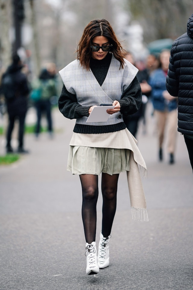 Street style photo of Christine Centenera wearing a plaid vest over a gray sweater with a pleated mini skirt, black tights, and white ankle boots at Paris Fashion Week Fall 2019.