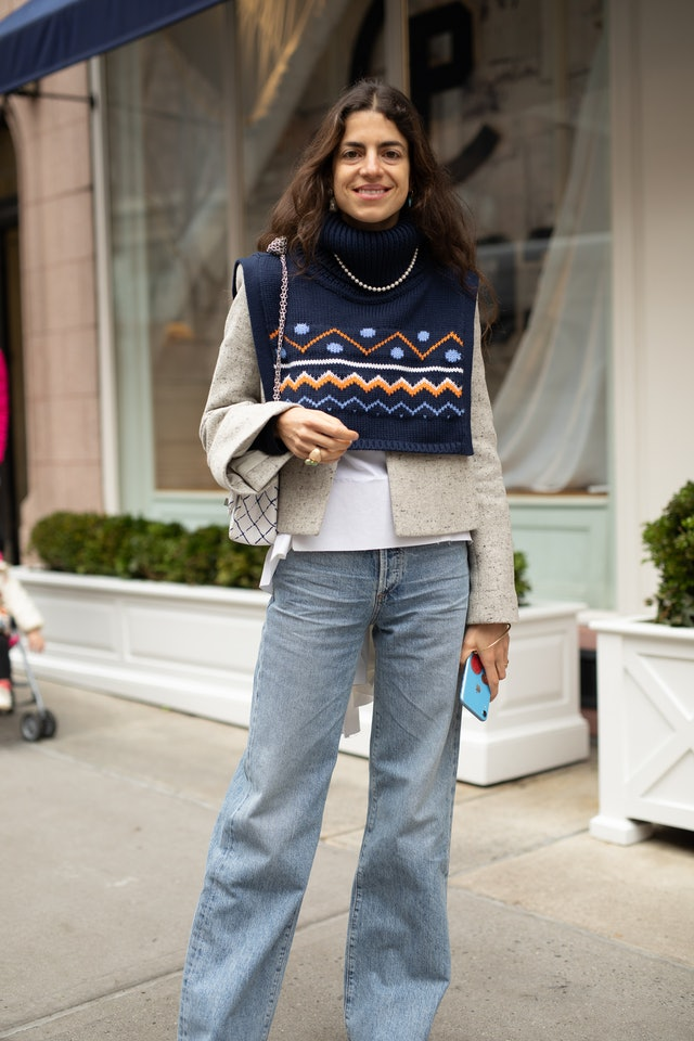 Street style photo of Leandra Medine wearing a sweater vest and blazer with jeans at New York Fashion Week Fall 2019.