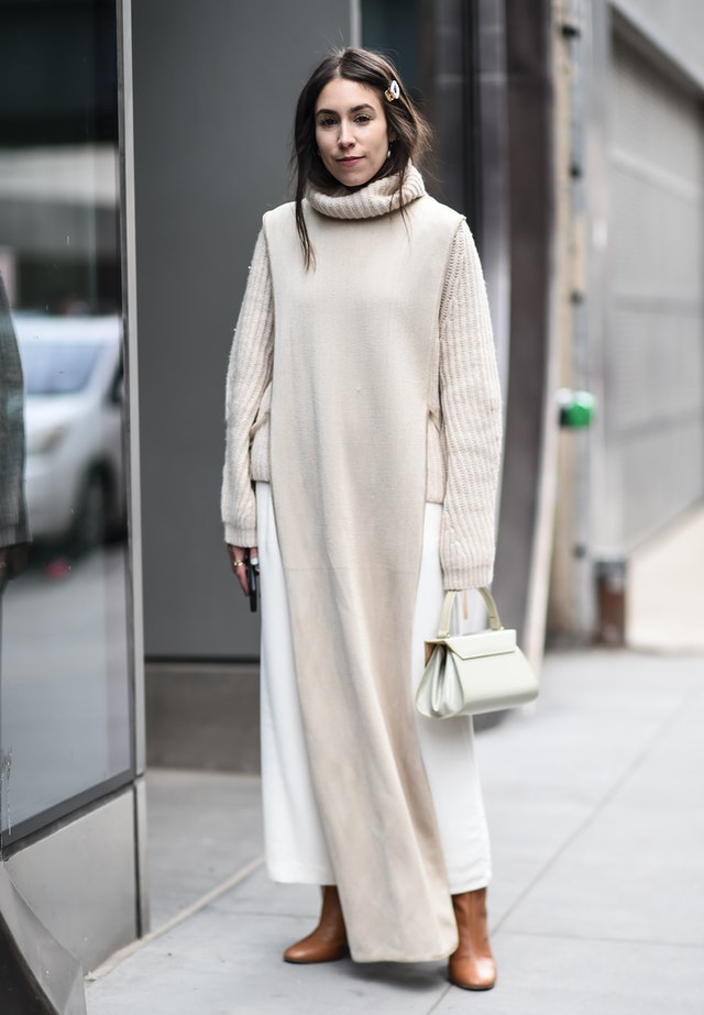 Street style photo of Lauren Caruso wearing a beige turtleneck and skirt under a long sweater tunic dress at New York Fashion Week Fall 2019.