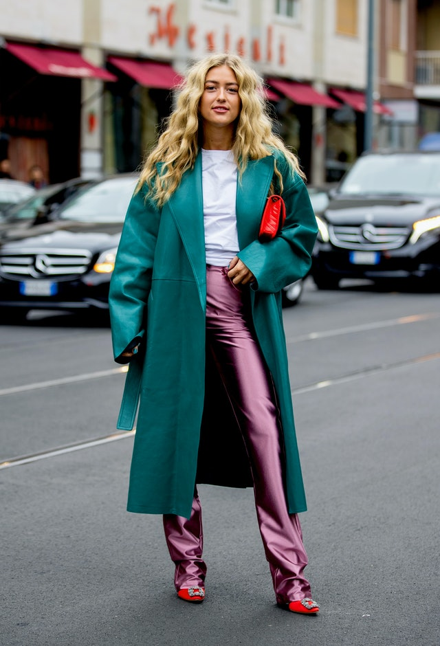Street style photo of Emili Sindlev wearing a dark teal coat and pink pants at Milan Fashion Week Spring 2020.