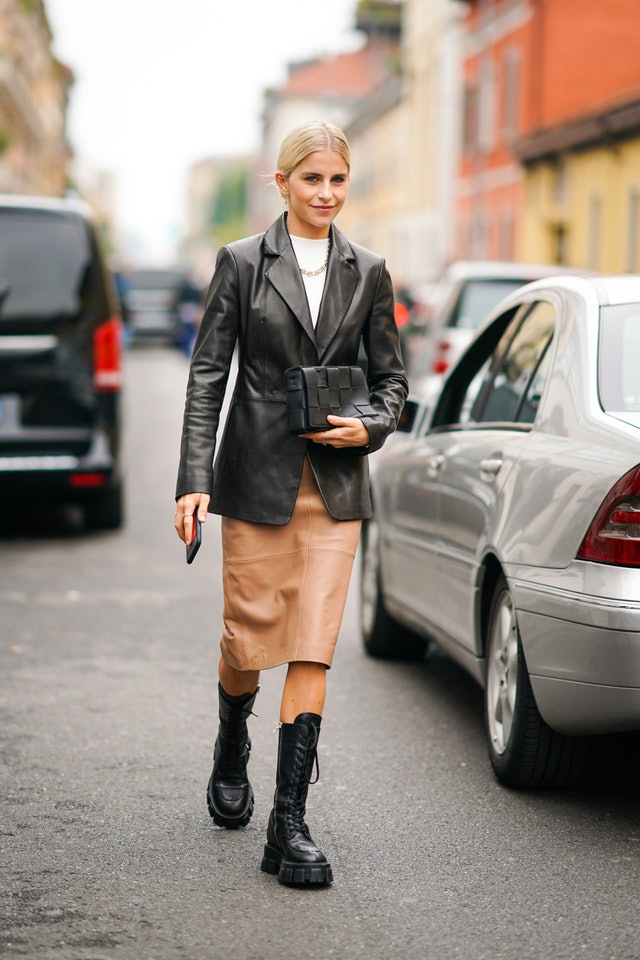 Street style photo of influencer Caroline Daur wearing a black leather blazer and tan pencil skirt with black combat boots at Milan Fashion Week Spring 2020.