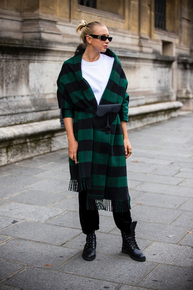 Street style photo of woman wearing green plaid coat and black combat boots at Paris Fashion Week Spring 2020.