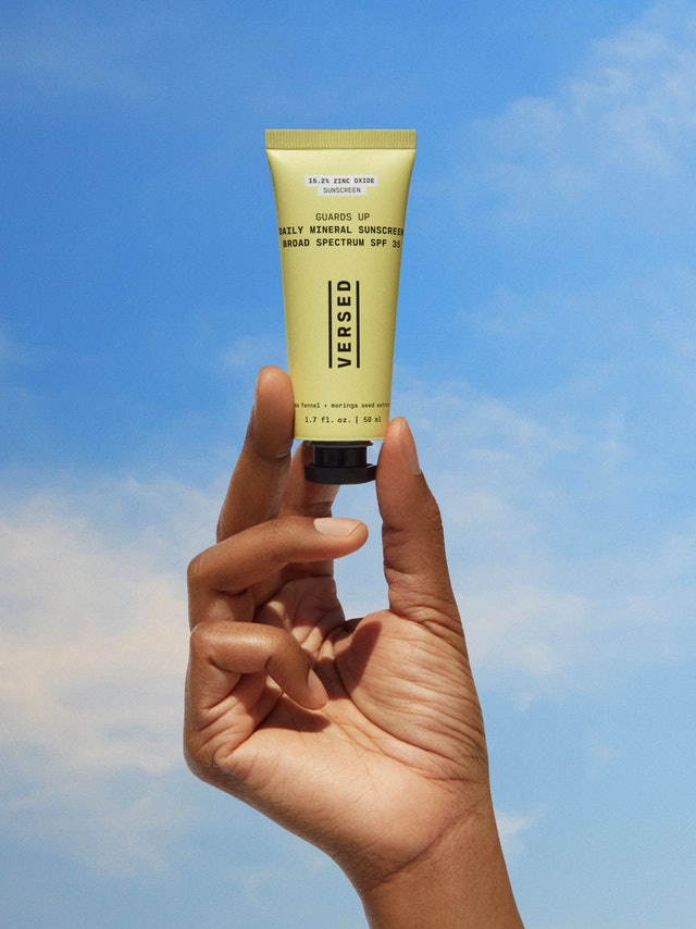Hand holding up Versed's new Guards Up Daily Mineral Sunscreen.
