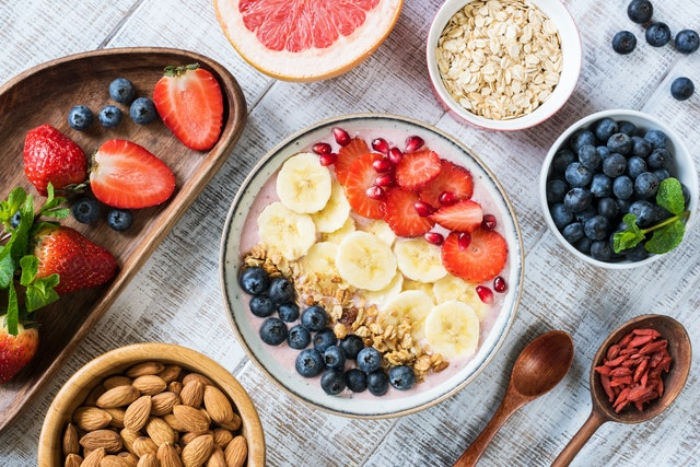 Smoothie bowl with banana slices, strawberry, blueberries, granola and pomegranate seeds. Top view. Healthy lifestyle, healthy eating, dieting, weight loss concept
