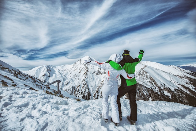 Couple in ski suits standing on a mountain peak, enjoying the view.