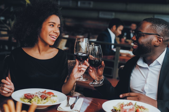 African American Couple Dating in Restaurant. Romantic Couple in Love Dating. Cheerful Man and Woman with Menu in a Restaurant Making Order. Romantic Concept. Cheers Classes Red Wine.