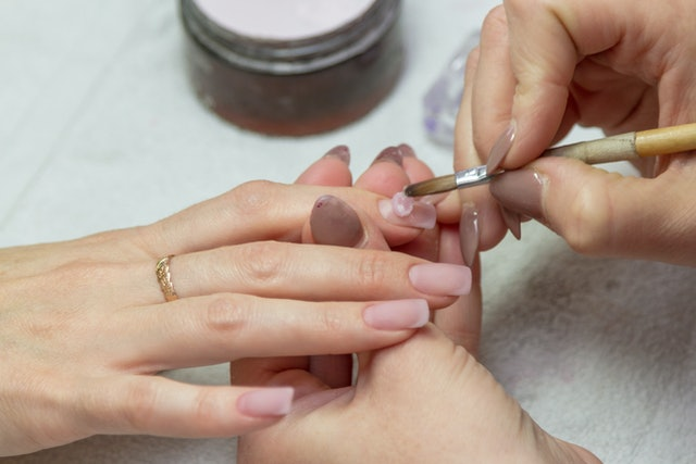 applying a brush on acrylic nails in the salon