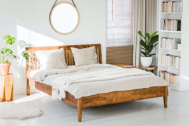 White bedroom interior with wooden king-size bed, fresh green plants, window with blinds and library on white bookcase