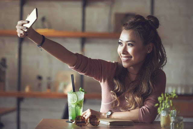 Very beautiful Vietnamese young woman taking selfie in cafe