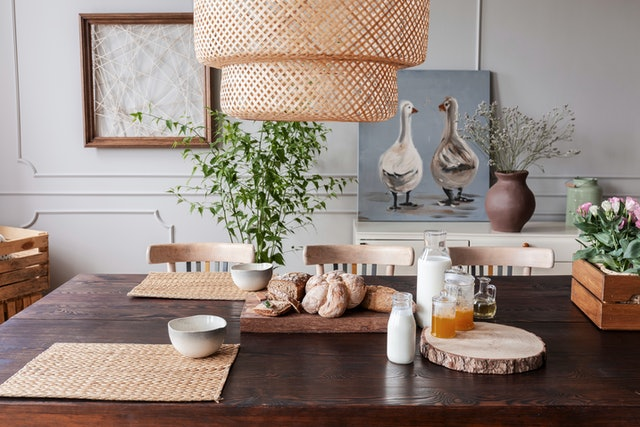 Lamp above wooden table with food and bowls in grey dining room interior with posters. Real photo
