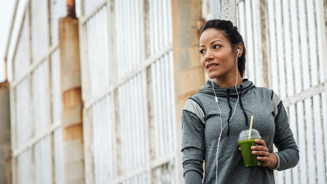 Happy urban fitness woman drinking detox green smoothie on a workout rest. Sport and modern healthy lifestyle concept.