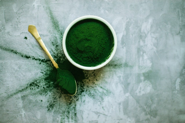 scattered spirulina powder in bowl and spoon on concrete background