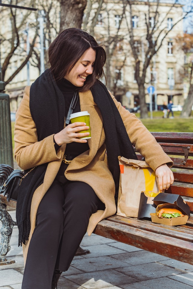 woman eating fast food on city bench. lifestyle concept