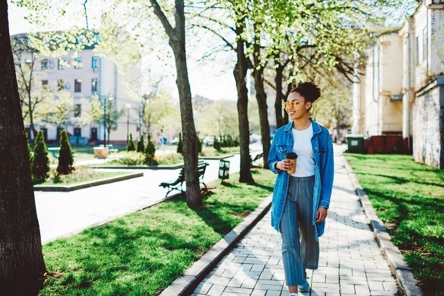 Happy female tourist enjoying strolling around summer city streets with takeaway coffee in hand during vacation on leisure, positive hipster girl dressed in denim look walking during free time