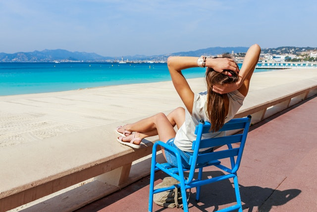 Tourist woman in Cannes, Cote d'Azur, France, South Europe. Nice city and luxury resort French riviera. Famous tourist destination with nice beach and Promenade de la Croisette on Mediterranean sea