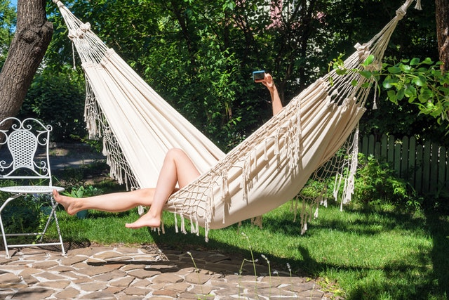 Vacation selfie. Enjoying the summer. Young woman using smartphone laying in hammock in the garden