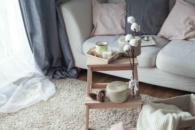 Home decor. A wooden bedside table, a sofa, a cotton, a mug of hot coffee, a knitted plaid. Warm house. Autumn. Cozy. House. The book and glasses. Interior. Spring