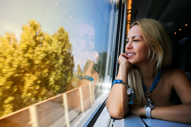 A girl sits on a train and looks out the window