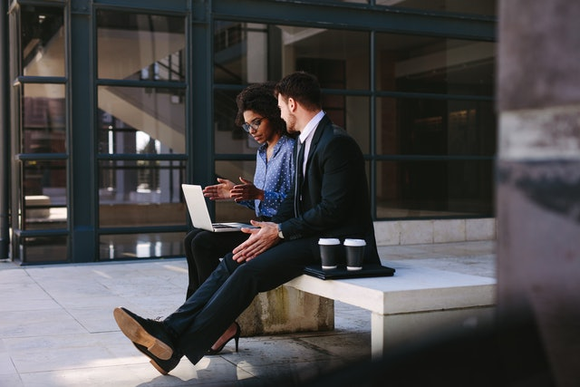 Two business people sitting on a bench in modern office building with a laptop. Woman with laptop discussing business with male colleague.