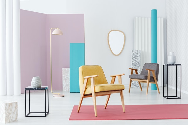 Yellow wooden armchair on pink rug in pastel retro living room interior with mirror on the wall
