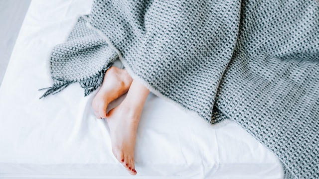 Home textile concept. Natural bed linen collection. Interior decor. Comfort rest. Woman feet peeking out from blanket.