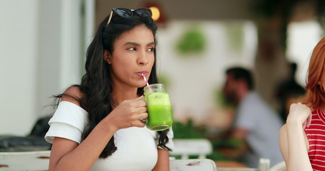 Multiracial girl drinking healthy green juice outdoors