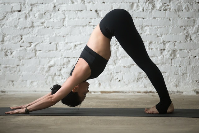Young yogi attractive woman practicing yoga concept, standing in Downward facing dog exercise, adho mukha svanasana pose, working out, wearing black sportswear, full length, white loft background