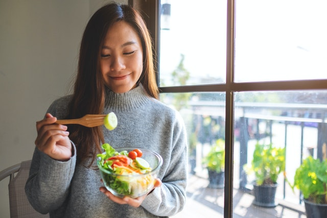 Closeup image of a beautiful asian woman eating and holding a bowl of fresh mixed vegetables salad
