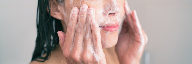 Face wash exfoliation scrub soap woman washing scrubbing with skincare cleansing product panoramic banner.