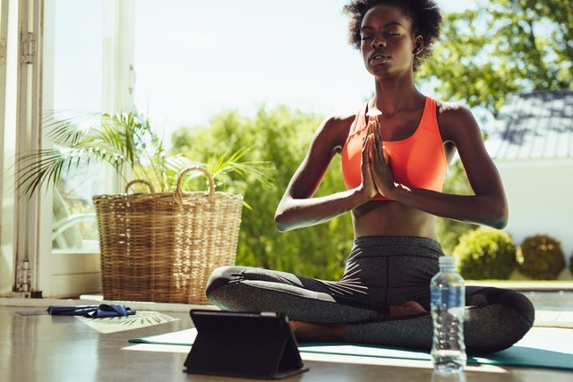 Healthy woman sitting on yoga meditation at home with a digital tablet in front. Fitness woman in sportswear meditating in lotus yoga pose indoors.
