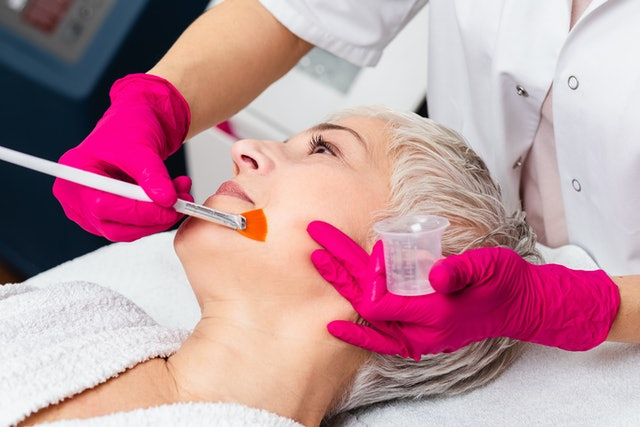Beautiful senior woman having chemical peeling beauty treatment. The expert beautician is applying chemical solution onto woman's face.