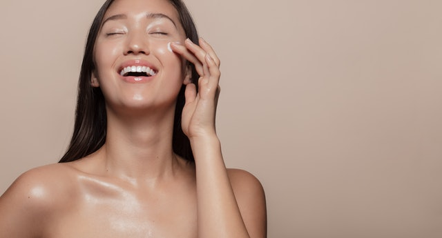 Beautiful girl with bare shoulders applying cream on her face and smiling against beige background. Smiling asian woman with glowing skin applying facial skincare cream with eyes closed.